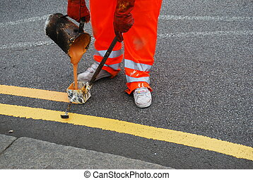 Double yellow - Worker painting double yellow line on the...