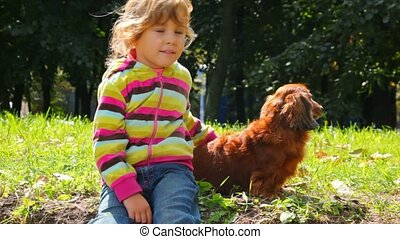 little girl stroking dog in park