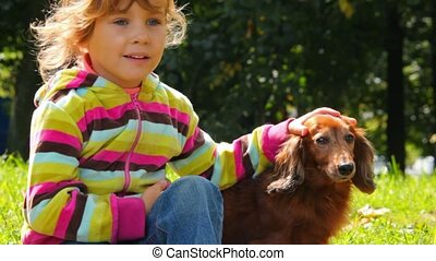 little girl stroking dog in park closeup