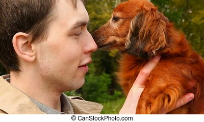 dog licking men\'s nose