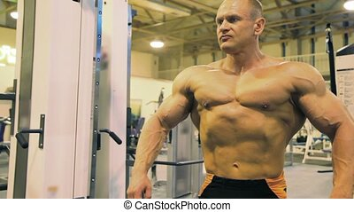 bodybuilder straining muscles in gym