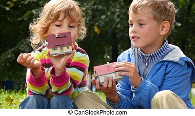 boy and girl playing with toy houses