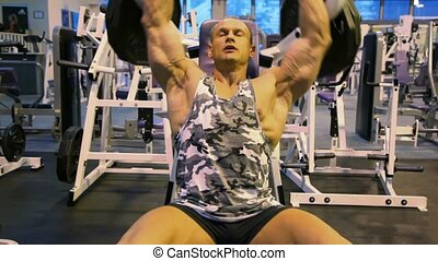 bodybuilder exercising with weight in gym