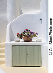 white house and vase with flowers in Santorini, Greece. -...