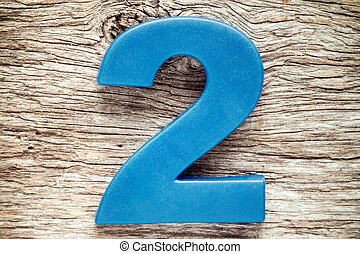 Blue number two on the wooden background