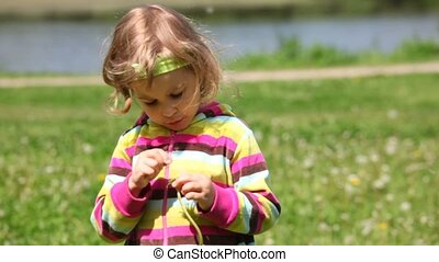 Girl in the purple blouse plays with dandelion. Greenfield, river