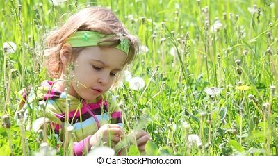 Little girl sitting on the grass in the green field looking...