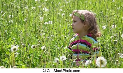 Little girl sitting on the grass in the green field looking to the left