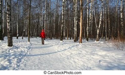 Woman in red coat walking in the winter forest