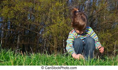 Little girl sits on grass and pulls out blades