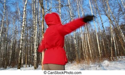 Woman in red coat go round in the winter forest