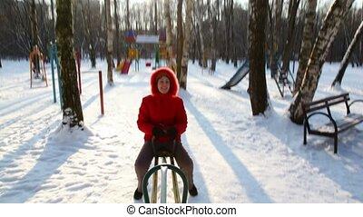 Woman in red coat rocks on winter seesaw