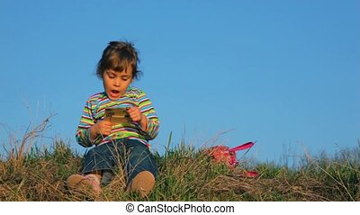Little girl is reading something on the paper