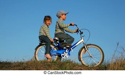 Boy and girl sitting on the bicycle, like they are riding