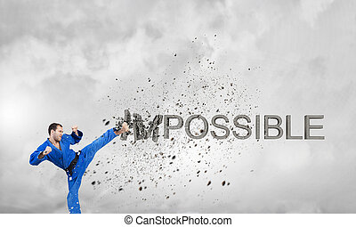 Nothing is impossible - Young determined karate man breaking...