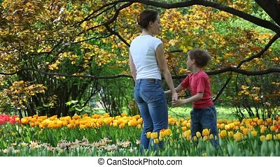 mother with son in autumnal park near tulips