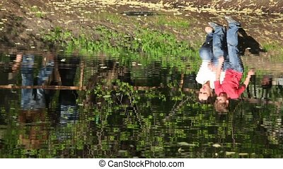 Mother and kid in the river reflection