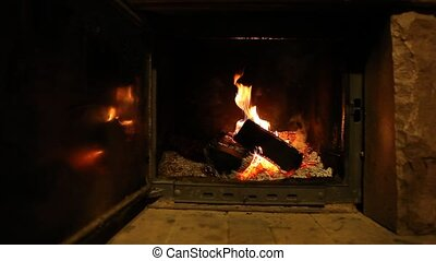 Wood logs fire burn in fireplace creating warm and romantic...