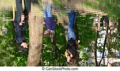 Reflection of family in water of river