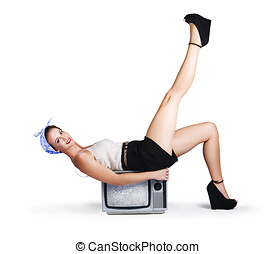 Pinup girl balancing on television set - Pinup girl with...