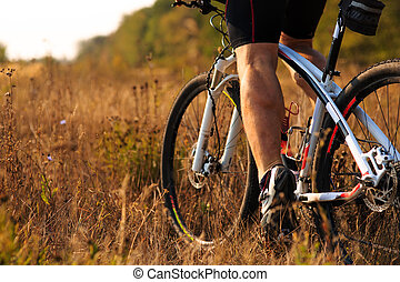 cyclist man legs riding mountain bike on outdoor trail -...
