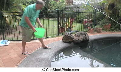 Salting A Swimming Pool - Middle aged man walks in and adds...