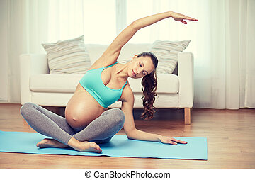 happy pregnant woman exercising at home - pregnancy, sport,...