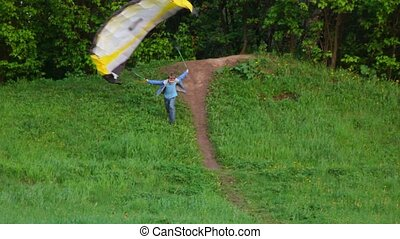 Boy trying to start the kite by running down from the hill, but fall over