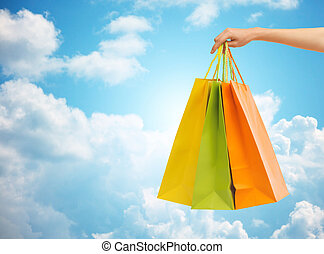 close up of hand holding shopping bags