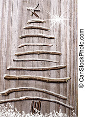 Christmas tree arranged from sticks on wooden snowy grey background.