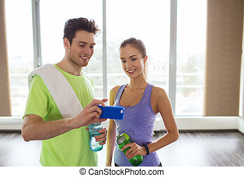 happy woman and trainer showing smartphone in gym - fitness,...