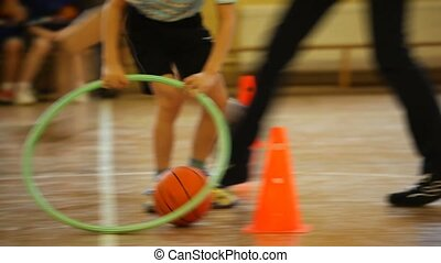 Boy rolling a ball by hoop