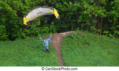 Boy trying to start the kite by running down from the hill