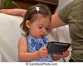 Toddler girl playing a smartphone - Beautiful cute toddler...