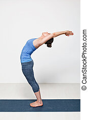 Sporty fit woman practices yoga asana Anuvittasana -...