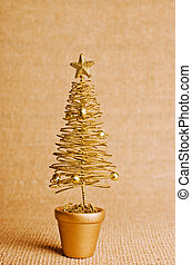 Gold Christmas tree on bright background with copy space.