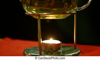brewing in teapot with candle, vertical panning