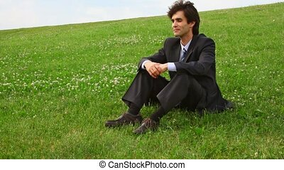 handsome man in suit get lying on green grass
