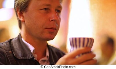 man drinks from  cup