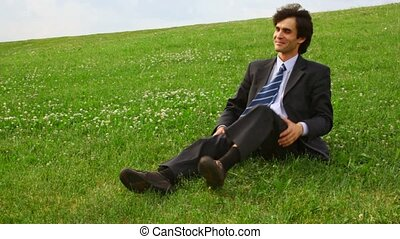 handsome man in suit get lying on green grass and lift up legs