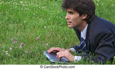handsome man profile typing on keyboard lying on green grass