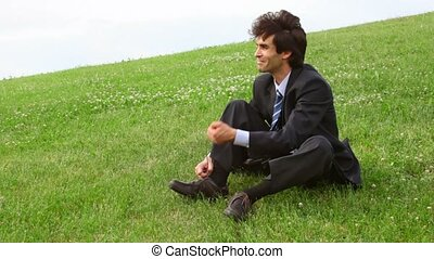 handsome man sitting on green grass and take off shoes,...