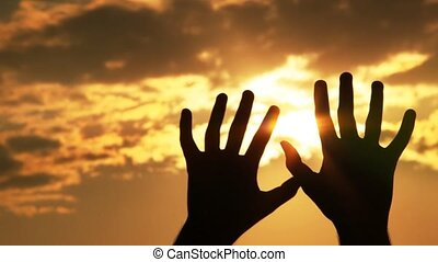 Silhouette of a hands against the sun