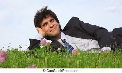 happy handsome man lying on green grass
