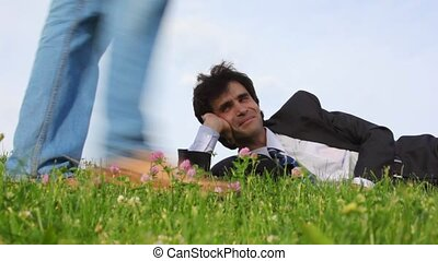 happy handsome man lying on green grass and legs of passerby