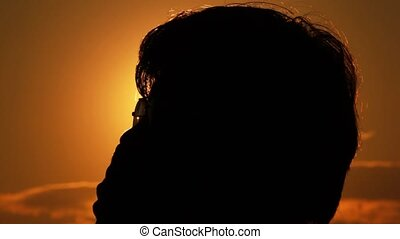 Silhouettes of a head, face and glasses of the man against the sun