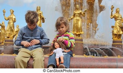 girl and boy playing, with fountain friendship at All-Russia Exhibition Centre on the background