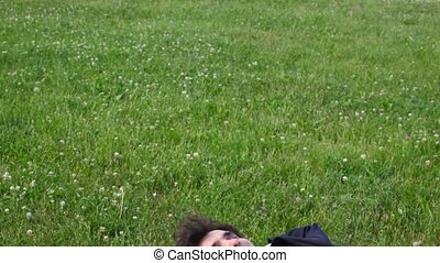 happy handsome man lying on green grass, panning