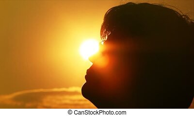 Silhouettes of a head and face of the man against the sun