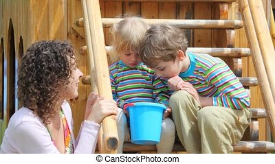 mother and 2 children looking at something in the small bucket